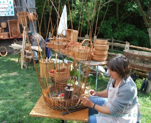 A basket weaver demonstrates her craft at an open air museum in Germany