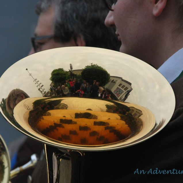 The town square reflected in the instrument of a band member