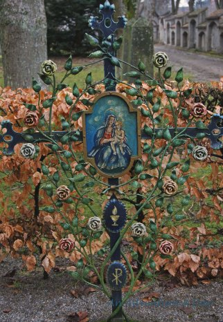 A metal cross with the likeness of Mary and Jesus on a grave marker in Pfullendorf.