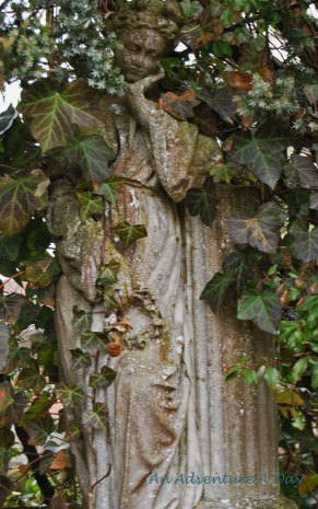 Half hidden by vines, a statue holds a thoughtful pose in a cemetery in Pfullendorf