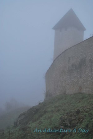 The castle looks mysterious in the morning fog.