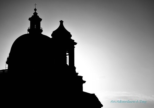 A black and white silhouette captures the outline of the church in the early morning.