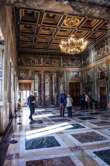 The walls in this room are painted with columns to look as if you are standing in an open portico overlooking several various scenes